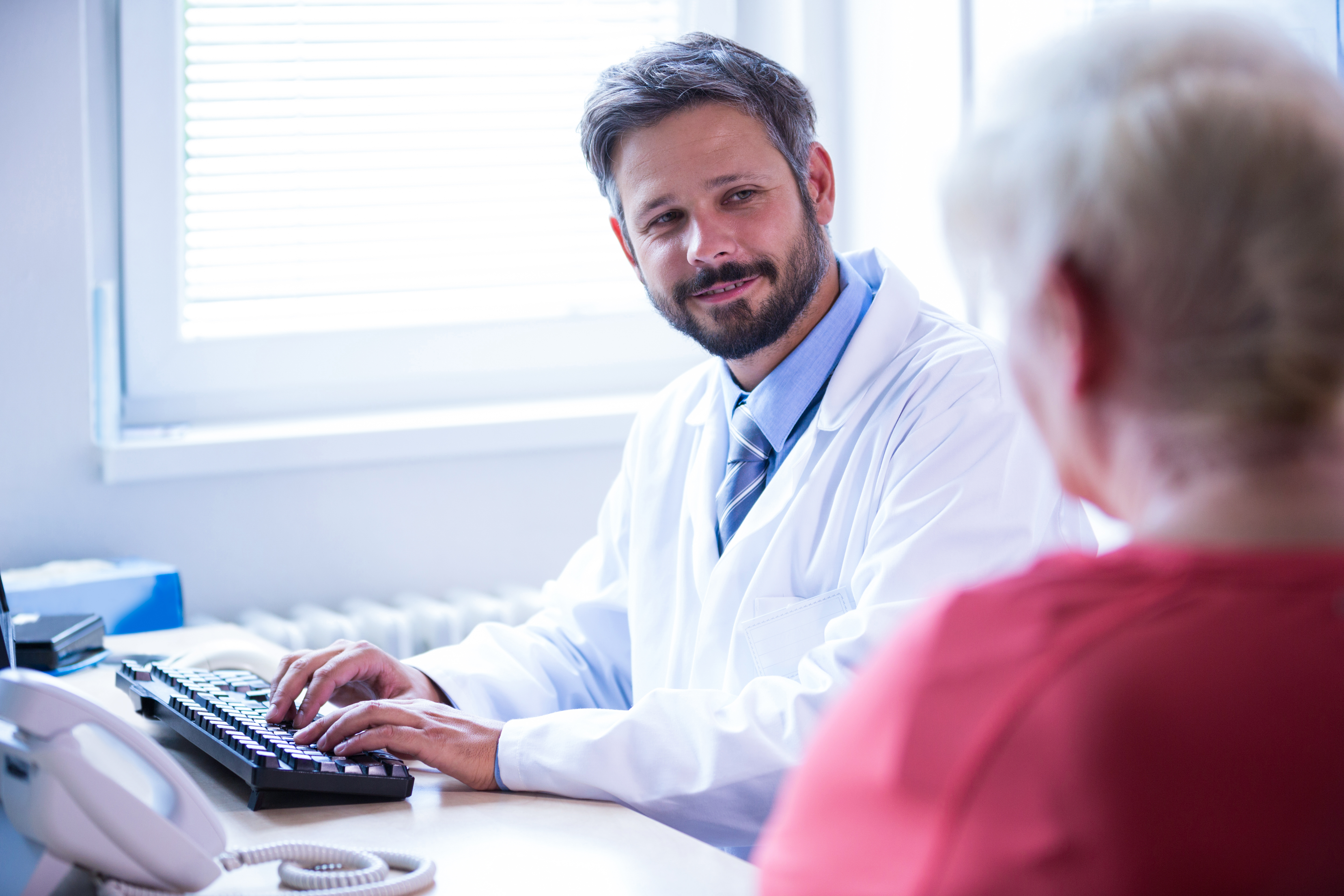 Doctor interacting with patient while working on computer in medical office at hospital